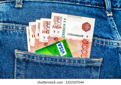 Samara, Russia - December 23, 2015: Credit card Visa with banknotes of russian roubles sticking out of the jeans pocket