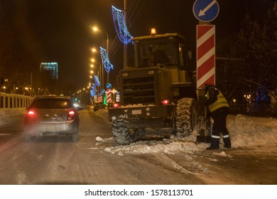 Samara, Russia - December 27, 2018: Snow removal from the streets in the city at night. The city snow removal service cleans the road in the city with the help of a snowplow