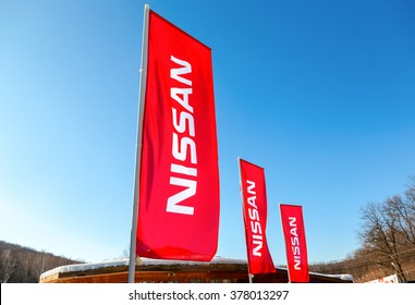 SAMARA, RUSSIA - FEBRUARY 14, 2016: Dealership flags Nissan over blue sky in sunny day. Nissan is a Japanese multinational automaker