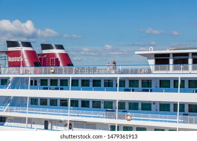 "Samara / Russia - July 2, 2019: Four-deck river cruise liner ""Semyon Budenny"" at the pier in the city of Samara. On a Sunny summer day. Tourist cruise company ""Vodohod""."