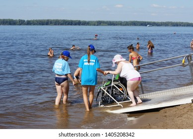 Samara, Russia, June, 21, 2016: opening of an accessible beach for disabled people (people with disabilities), barrier-free environment, volunteers help a disabled woman to enter the water