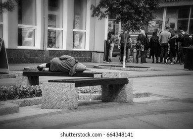 SAMARA, RUSSIA - JUNE 9, 2017: Homless old woman lies and sleeps on a bench in center of city
