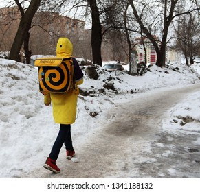 SAMARA, RUSSIA - MARCH 17, 2019: A deliveryman of a Russian food service Yandex.Eda taking the order to the client in early spring street