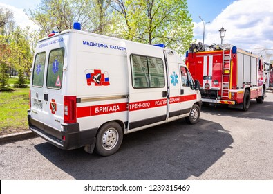 """Samara, Russia - May 9, 2018: Ambulance car and fire truck parked up at the street. Text on russian: """"Team of emergency response"""""""