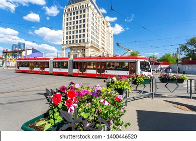 Samara, Russia - May 9, 2019: Cityscape with flowers, red tram and modern building of Lotte Hotel Samara in summer sunny day
