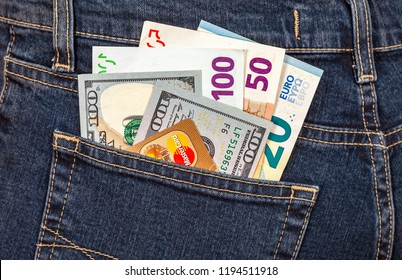 Samara, Russia - November 24, 2017: Different banknotes of Euro and american currency with credit card sticking out of the back jeans pocket. Money for travel and shopping