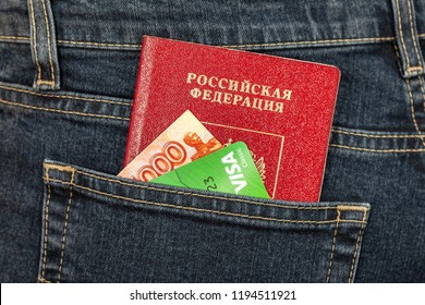 Samara, Russia - November 24, 2017: Russian passport, money and credit card Visa in back jeans pocket. Travel concept