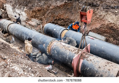 Samara, Russia - October 1, 2017: Repair work of heating duct. The workers, welders made by electric welding on large iron pipes at a depth of excavated trench