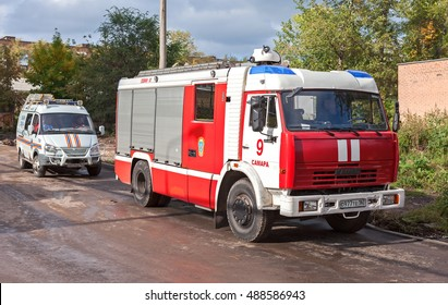 SAMARA, RUSSIA - SEPTEMBER 22, 2016: Red fire truck EMERCOM of Russia and rescue vehicle parked up on the street in summer