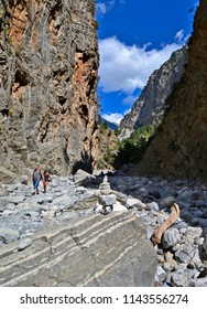 SAMARIA, GREECE - SEPTEMBER 23, 2016: Two tourists hike in Samaria Gorge in Crete. This majestuous gorge is considered one of the great attractions of Crete island.