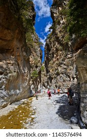 SAMARIA, GREECE - SEPTEMBER 23, 2016: Tourists walking along the trail in the Samaria Gorge in Crete. This majestuous gorge is considered one of the great attractions of Crete