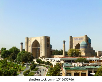 Samarkand, Uzbekistan - AUGUST 15, 2018: View of the Beautiful old city - ancient Bibi-Khanym Mosque and green park against the background of blue sky in Samarkand and central pedestrian road.