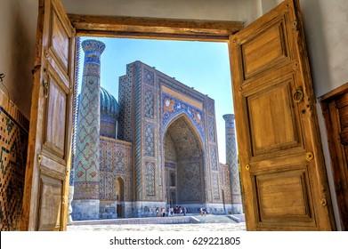 SAMARKAND, UZBEKISTAN - AUGUST 28: View to Sher Dor Madrasah thru the carved wooden door of Registan - landmark of Samarkand. HDR photo. August 2016