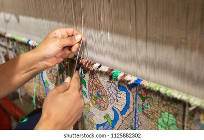 SAMARKAND, UZBEKISTAN - JUNE 12, 2018: Hands of a woman are weaving carpet tools and threads handmade in Uzbekistan Samarkand Bukhara carpet, textile production folk traditional Muslim work copy space