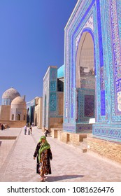 SAMARKAND, UZBEKISTAN - MAY 20, 2011: The Shah-i-Zinda with a colorfully dressed Uzbek woman in the foreground