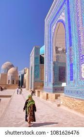 SAMARKAND, UZBEKISTAN - MAY 20, 2011: The Shah-i-Zinda with a colorfully dressed Uzbek woman in the foreground