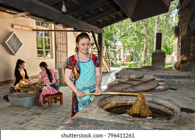SAMARKAND, UZBEKISTAN - MAY 20, 2017: Uzbek girl takes the mulberry tree barks from hot water in Konighil village near Samarkand, where they make silk paper in traditional way.