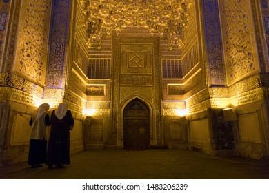 SAMARKAND, UZBEKISTAN - MAY 20, 2019: Women prayiyin the Tilya Kori Mosque and Madrasah located in Registan Square, in Samarkand, Uzbekistan.