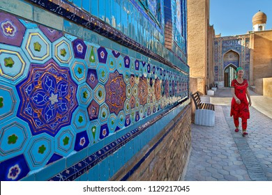 SAMARKAND, UZBEKISTAN - MAY 25, 2018: Woman in local dress walks in the courtyard of the Holy Cemetery of Shah-i-Zinda, in Samarkand, Uzbekistan.