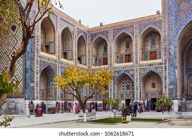 SAMARKAND, UZBEKISTAN - NOVEMBER 23, 2017: Ulugh Beg Madrasa courtyard view with small souvenir shops, Samarkand, Uzbekistan