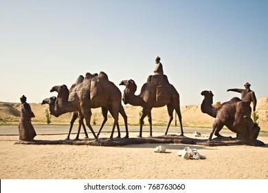 SAMARKAND, UZBEKISTAN - October 2015: Bronze statue of Uzbek man leading caravan of camels in desert, Samarkand, Uzbekistan