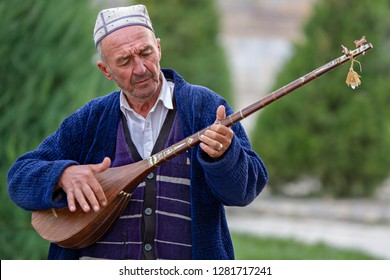 SAMARKAND, UZBEKISTAN - OCTOBER , 2017: Uzbek man plays local musical instrument, known as Dutar, in Samarkand, Uzbekistan