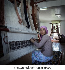 SAMARQUAND, UZBEKISTAN - MARCH 14, 2015: Unidentified female weaver knotting a handmade carpet.