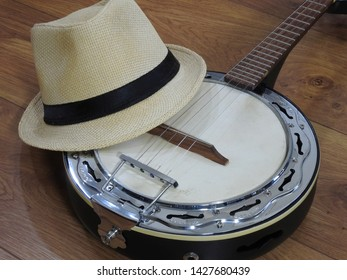 A samba banjo (a Brazilian string musical instrument) and a samba player (sambista) hat on a wooden surface. This instrument is widely used to accompany samba, the most popular Brazilian rhythm.
