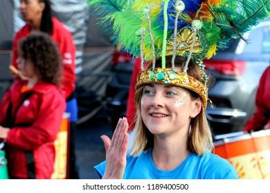 Samba dancer wearing colourful head piece performing with the Edinburgh Samba School Band during Jura Music Festival : Craighouse, Isle Of Jura, Scotland, UK : 23 September 2018 : Pic Mick Atkins