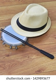 A samba player (sambista) hat and a tamborim with drumstick (a Brazilian percussion musical instrument) on a wooden surface. This instrument is widely used to accompany samba music.