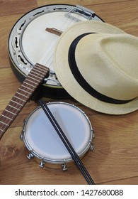 A samba player (sambista) hat and two Brazilian musical instruments: a samba banjo and a tamborim with drumstick on a wooden surface. The instruments are widely used to accompany samba music.