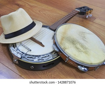 A samba player (sambista) hat and two Brazilian musical instruments: a samba banjo and a pandeiro (tambourine), on a wooden surface. The instruments are widely used to accompany samba music.