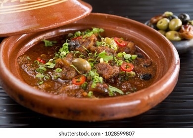 Sambal chicken tajine served with olives, in a rustic beautiful tagine pot, photographed with a shallow depth of filed. World cuisine.