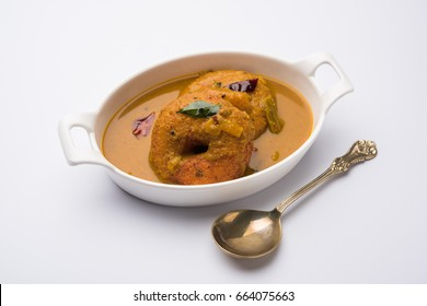 Sambar / Medu Vada, a popular South Indian food served with Green, Red and coconut chutney over moody background. Selective focus