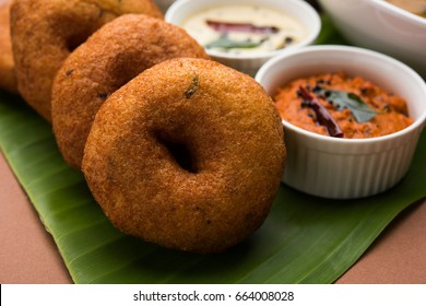 Sambar Vada also known as Medu Vada, a popular South Indian food served with Green, Red and coconut chutney over Banana Leaf. moody background. Selective focus