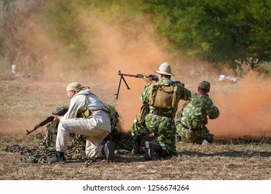 SAMBEK, ROSTOV REGION, RUSSIA, AUGUST 19, 2018: Historical festival Sambek Heights. Reconstruction of Afghan war. Three Soviet soldiers is beating off the attack of the mujahideen using a smoke screen