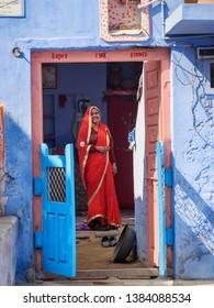 Sambhar, India - February 03, 2019: Indian woman in red sari in the door of blue house in Sambhar Lake Village. Rajasthan