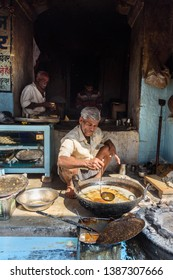 Sambhar, India - February 03, 2019: Indian men preparing samosas with vegetarian ingredients on the street in Sambhar Lake Village. Rajasthan