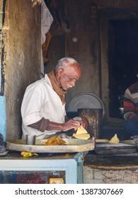 Sambhar, India - February 03, 2019: Indian man preparing samosas with vegetarian ingredients on the street in Sambhar Lake Village. Rajasthan