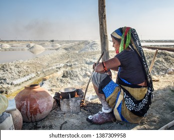 Sambhar, India - February 03, 2019: Indian woman making tea on fire at Sambhar Salt Lake. Rajasthan