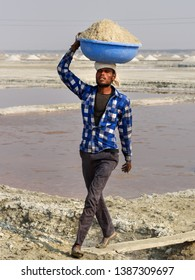 Sambhar, India - February 04, 2019: Indian man carrying basin with salt on her head on Sambhar Salt Lake. Rajasthan