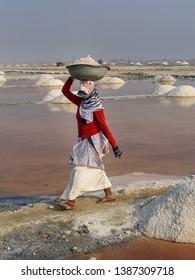 Sambhar, India - February 04, 2019: Indian woman carrying basin with salt on her head on Sambhar Salt Lake. Rajasthan