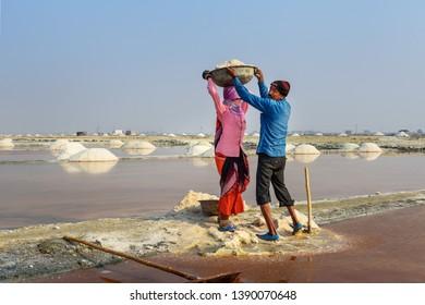 Sambhar, India - February 04, 2019: Indian workers putting basin with salt on head of woman on Sambhar Salt Lake. Rajasthan