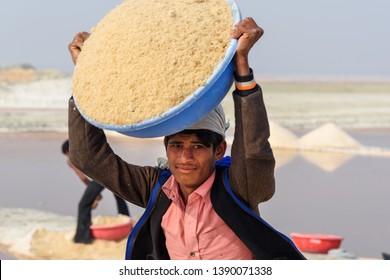 Sambhar, India - February 04, 2019: Portrait of Indian man carrying basin with salt on her head on Sambhar Salt Lake. Rajasthan