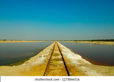 Sambhar, Rajasthan - December 14, 2018: A narrow passage going between two salt land parts, it seems like it is meeting the sky at the horizon.