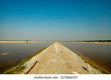 Sambhar, Rajasthan - December 14, 2018: A narrow passage going between two salt water parts, it seems like it is meeting the sky at the horizon.