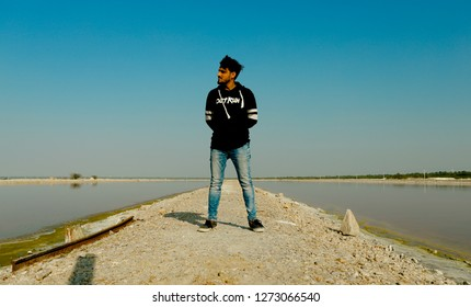 Sambhar, Rajasthan - December 14, 2018: A person is standing on the narrow passage going between two salt water parts.