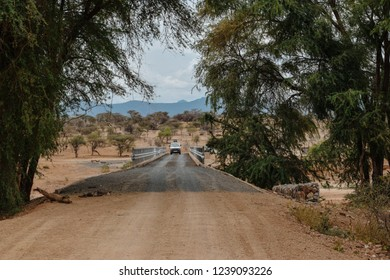 Samburu National Reserve, Samburu, Northern Kenya - April 4, 2015 : A tour van driving on a dirt road against an arid landscape