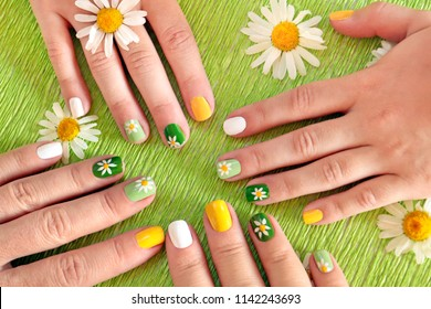 The same design of the nails of the mother and daughter with daisies. Summer cheerful manicure on a green background.