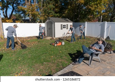 The same man performing many landscaping jobs to rake leaves and clean back yard in autumn fall cleanup appearing to work as single team in multiple exposure photography effect humor funny view